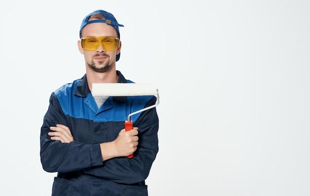 Мужчина ремонтирует желтые очки и валик для покраски стен
