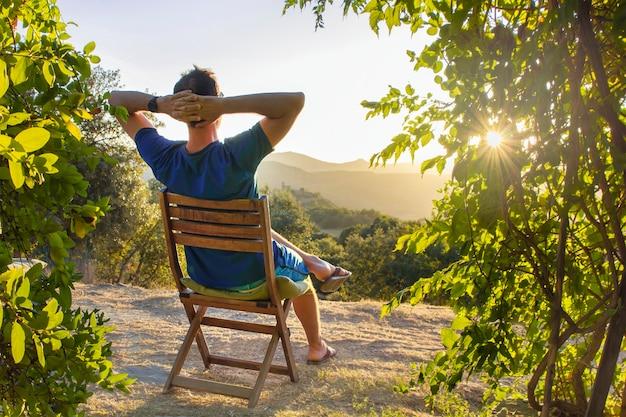 Мужчина отдыхает после прогулки, сидя на деревянном стуле и смотрит на закат рядом со своим домом в горах