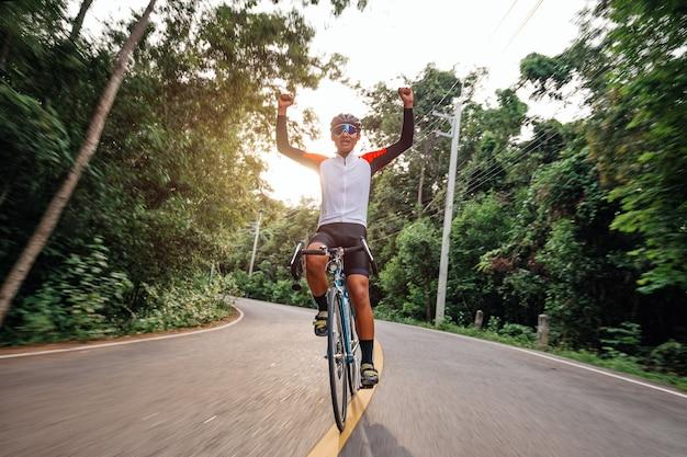 한 남자가 도로에서 자전거를 타고 있습니다. 저녁 운동을 위해 빈티지 스포츠 자전거를 타는 남자. 저녁 햇살이 비치는 자연, 초원, 숲 속에서 신선한 공기를 마시기 위해 자전거를 타는 남자