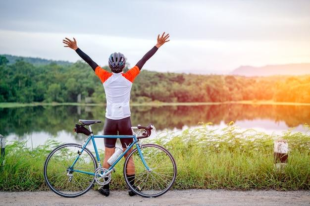 한 남자가 도로에서 자전거를 타고 있습니다. 저녁 운동을 위해 빈티지 스포츠 자전거를 타는 남자. 저녁 햇살이 비치는 자연, 강, 숲 속에서 신선한 공기를 마시기 위해 자전거를 타는 남자