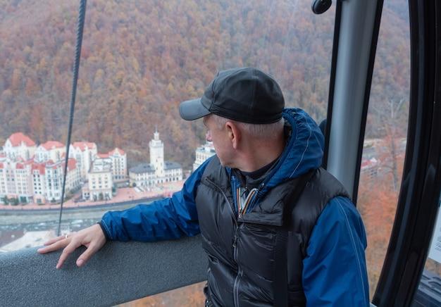男はケーブルカーに乗って、透明な窓から街を眺めます。