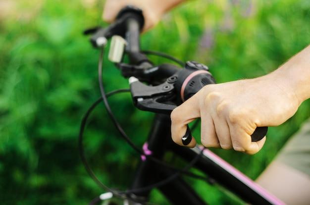 男は夏の森の道でマウンテンバイクに乗って、ブレーキを握る