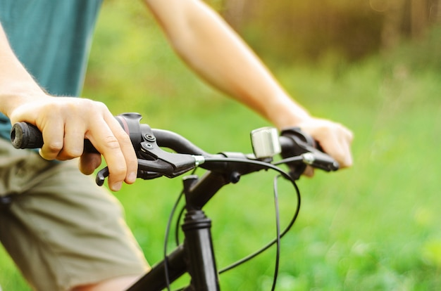 Мужчина едет на горном велосипеде по летней лесной дороге, держит тормоз