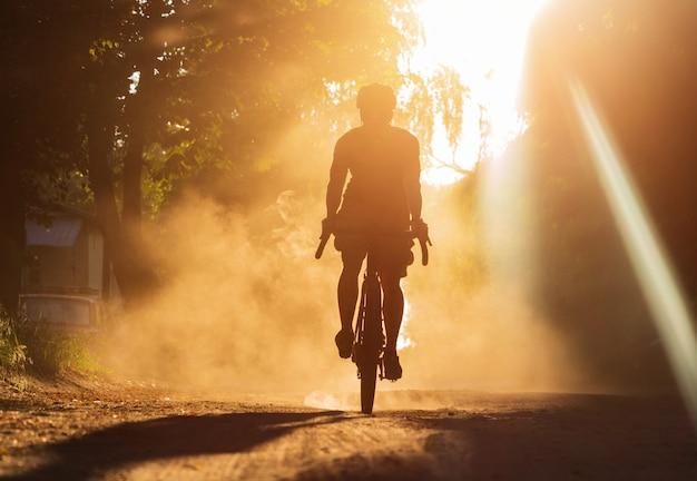 夕暮れ時に砂利道で自転車に乗る男。ほこりの雲の中の砂利自転車のサイクリストのシルエット。