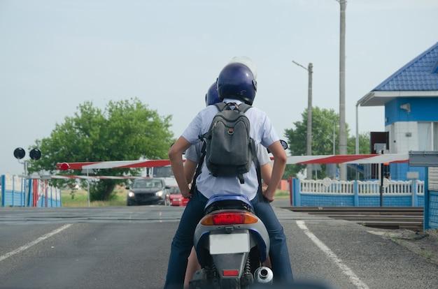 後ろから見た敷石から道路をスクーターに乗る男。美しい天気はあなたが旅行することを奨励します。