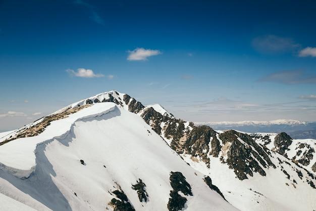 雪に覆われた山の頂上に乗っている男