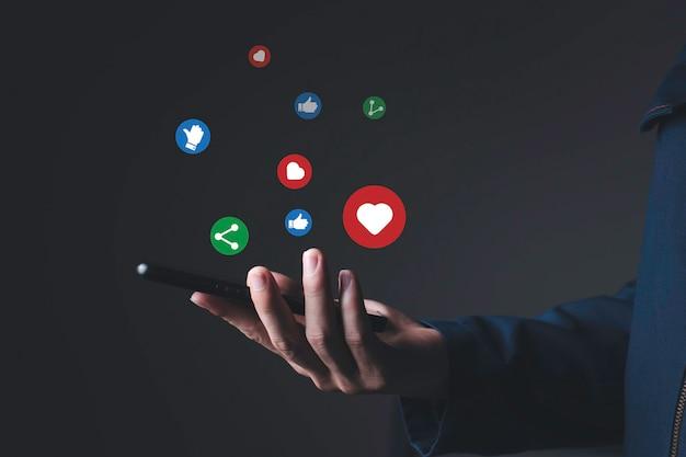 Мужчина справа улавливает мобильный чат со своим другом, социальные сети в интернете с векторными значками, такими как, любовь и совместное использование, концепция технологий и интернета