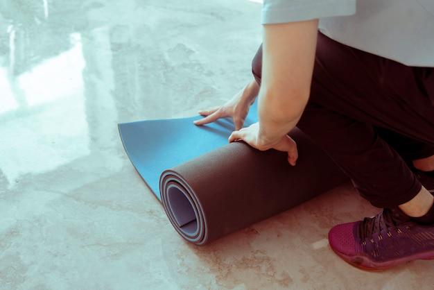 ヨガのクラスのトレーニングで床にヨガマットを転がしている男性