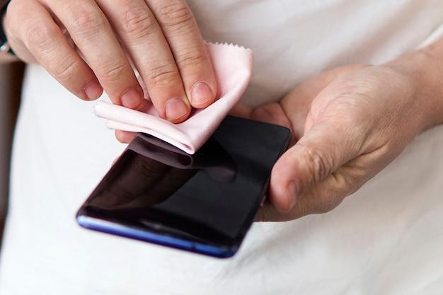 한 남자가 걸레로 검은색 스마트폰 화면을 문지르고 있다. 코로나바이러스 및 바이러스성 질병 예방. 먼지에서 휴대 전화 청소.