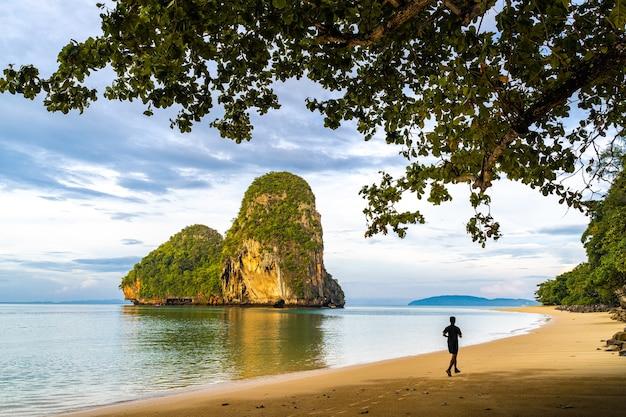 Pranang cave beach, railay, krabi, thailand에서 아침에 뛰는 남자