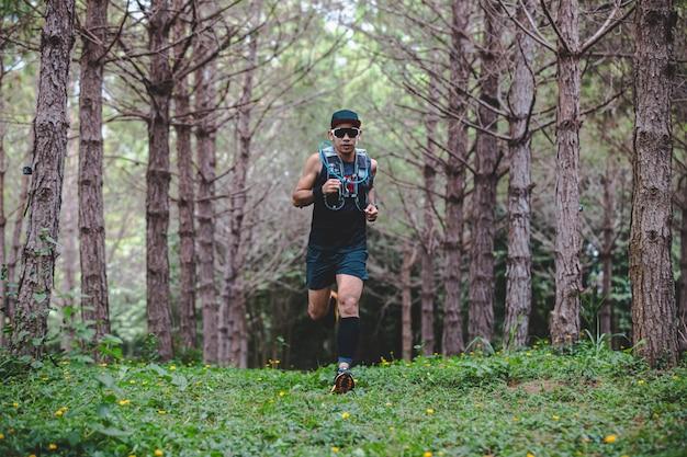 森をトレイルランニングするスポーツシューズを履いた男性ランナー