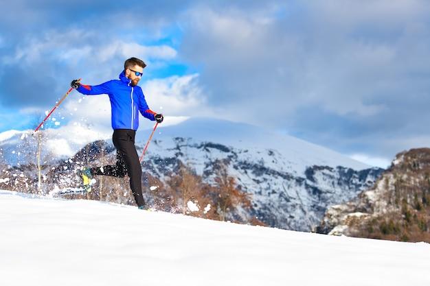 スノーシューで下り坂を走る男