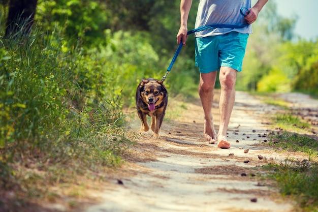 Мужчина бежит босиком с собакой по грунтовой дороге летом