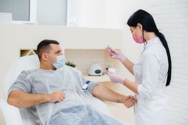 男性の血液は、ウイルスの分析と検査のために静脈から採取されます。免疫系と抗体の形成。