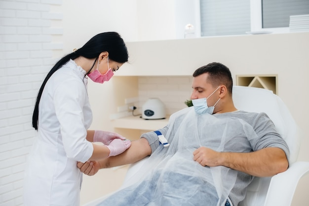 У мужчины берется кровь из вены для анализа и тестирования на вирусы. формирование иммунной системы и антител.