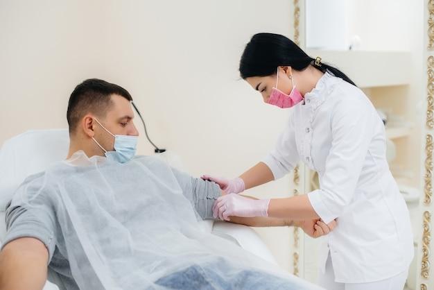 男性の血液は、ウイルスの分析と検査のために静脈から採取されます