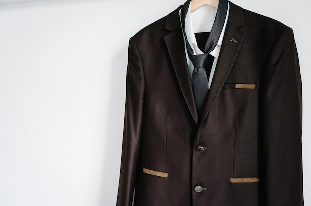 남자의 갈색 재킷, 셔츠와 넥타이는 배경 흰색 벽에 옷걸이에 달려 있습니다.