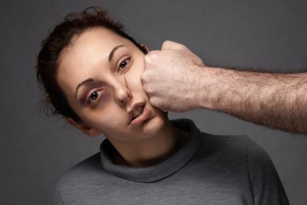 Кулак мужчины бьет женщину по лицу.