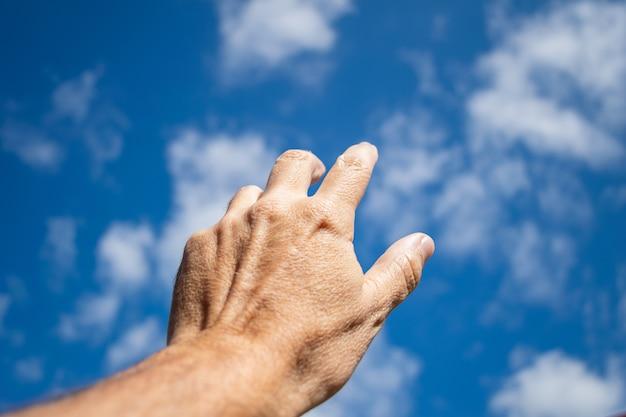 雲の少ない青い空に近づく男の手。信仰の象徴