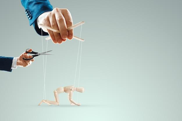 남자의 손이 인형과 인형 사이의 실을 가위로 자릅니다. 노예 제도, 자유, 그림자 정부, 세계 음모, 조작, 통제로부터의 해방의 개념.