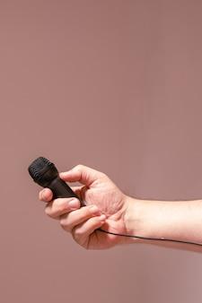 검은 마이크를 들고 남자의 손. 의사 소통, 인터뷰, 가상 대화의 개념.