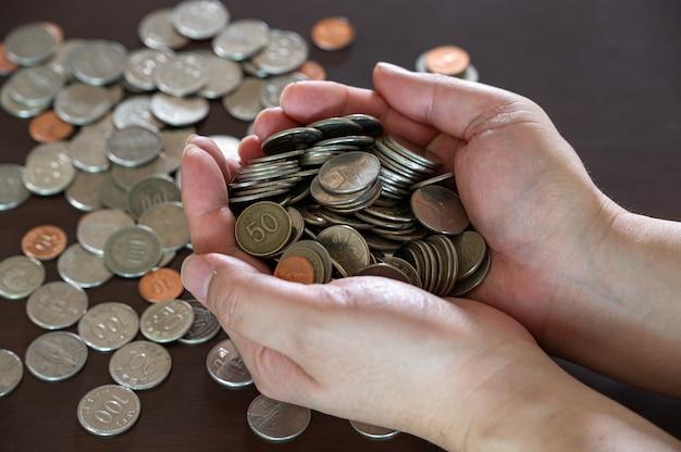 Рука человека, проведение кучу монет на деревянном столе.