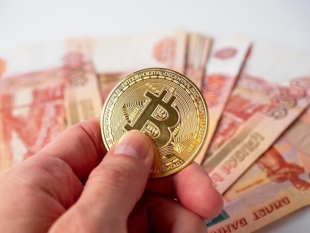 Рука человека держит золотой биткойн. на заднем плане пять тысяч российских рублевых купюр. концепция криптовалюты