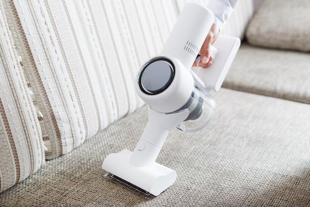 남자의 손은 집에 있는 소파를 청소하기 위한 현대적인 무선 진공 청소기를 들고 있습니다.
