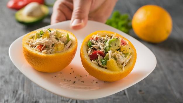 В мужской руке тарелка с двумя половинками апельсина, наполненными салатом.