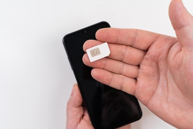 한 남자의 손이 검은색 스마트폰 근처에 sim 카드를 들고 있다