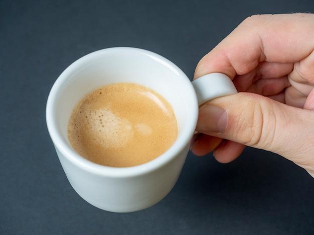 男の手は、暗い背景に淹れたてのエスプレッソの白いカップを持っています。茶色の泡。爽快なドリンク。上面図