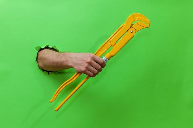 男の手は、破れた緑色の紙を通して黄色のチューブキーを持っています。破れた緑色の紙を手渡します。テキスト、ロゴ、デザインの場所が記載された写真。コンセプトの修理とツール