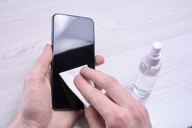 Мужская рука держит и щелкает дезинфицирующим спреем и дезинфицирует телефон для дезинфекции различных поверхностей, к которым люди прикасаются. антибактериальный антисептический гель для рук