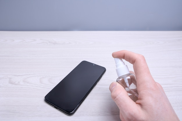 Мужская рука держит и щелкает дезинфицирующим аэрозолем и дезинфицирует телефон для дезинфекции различных поверхностей, к которым люди прикасаются. антибактериальный антисептический гель для рук.