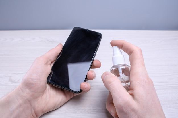 男の手が消毒スプレーを握ってパチンと音を立て、電話を消毒してさまざまな表面を消毒する