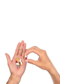 男の手は、さまざまな錠剤の大きな山でいっぱいです。コピースペースのある縦の写真。