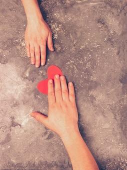 남자의 손이 여자의 손에 하트를 전달한다