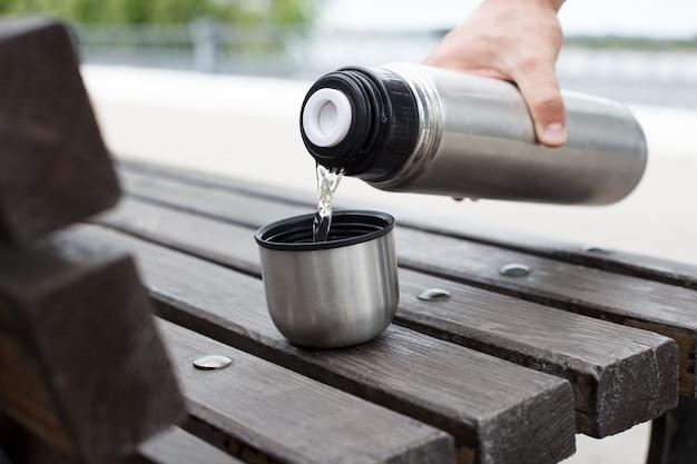 Мужская рука наливает чай из термоса в чашку на скамейке.