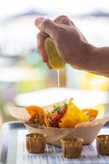男の手がレモンジュースを伝統的なメキシコのナチョスブルドサルサに絞ります