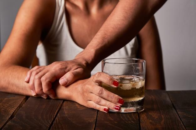 パートナーがバーで酒を飲むのを止めようとしている男性の手。アルコール依存症と中毒の概念。