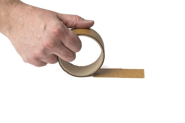 男の手が白い表面に分離された粘着テープをほどく