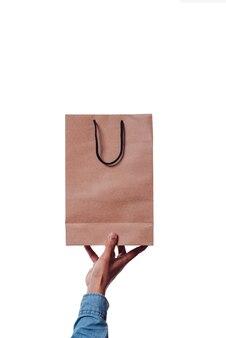 파란색 소매를 가진 남자의 손이 판지 쇼핑백을 들고 있습니다. 쇼핑 컨셉