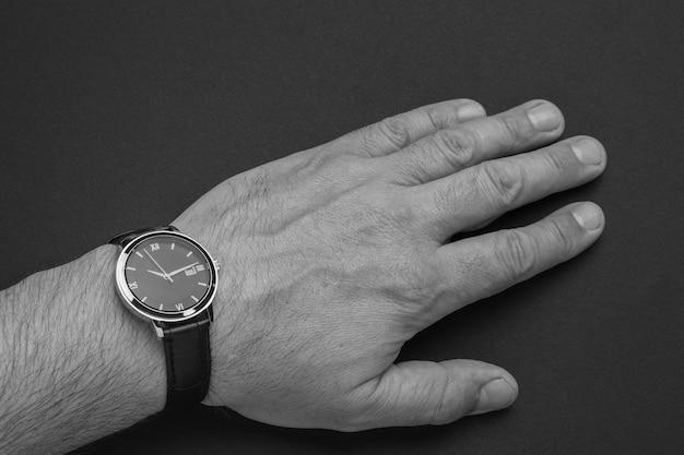 Рука человека с наручными часами со стрелками на черной поверхности. модный и стильный мужской аксессуар.