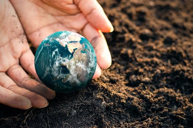 세계 환경의 날, 땅에 누워 있는 작은 지구를 한 남자의 손이 감싸고 있습니다. nasa에서 제공한 이 이미지의 요소입니다.
