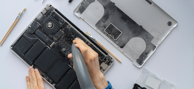 컴퓨터 서비스에서 일하고 개인 노트북에서 먼지를 제거하는 남자의 손