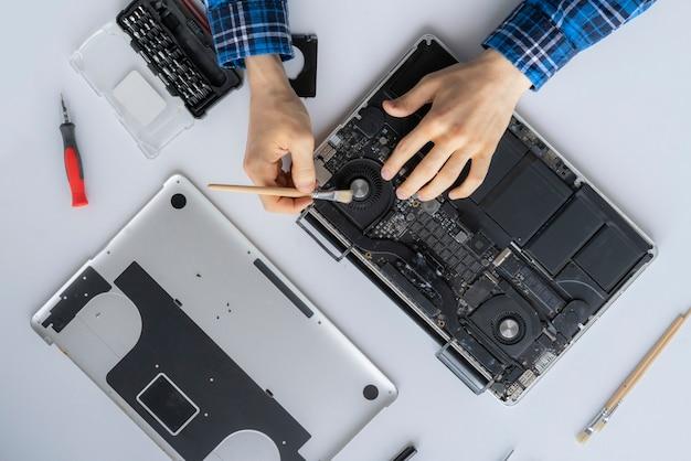 コンピュータサービスで働いて、個人のラップトップからほこりを取り除く男の手
