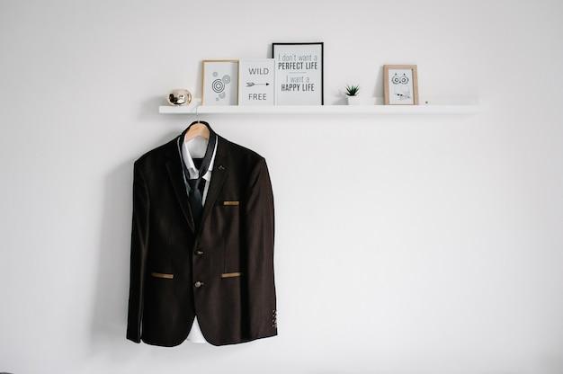 남자의 재킷, 셔츠 및 넥타이는 옷걸이 또는 방의 배경 흰색 벽에있는 선반에 달려 있습니다.