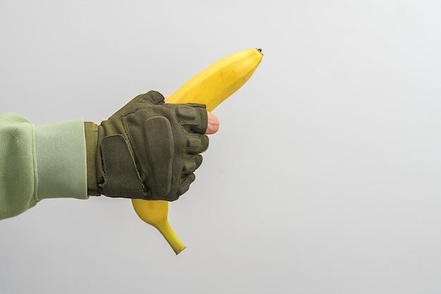 男の軍の手は灰色の背景にバナナを持っています。