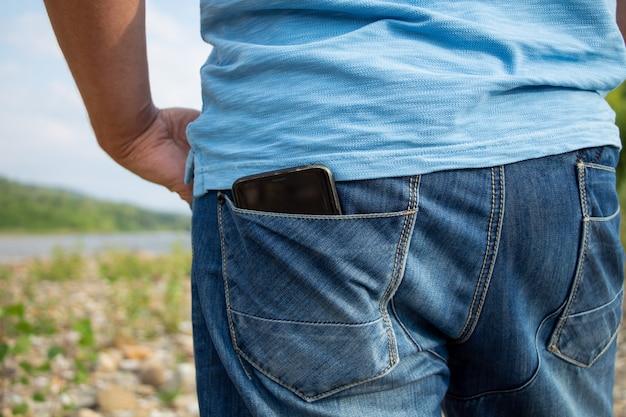 ズボンのポケットに入れた男性の携帯電話。