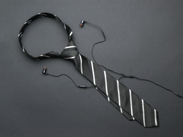 Полосатый мужской галстук и наушники на темном фоне. предметы для мужчин.